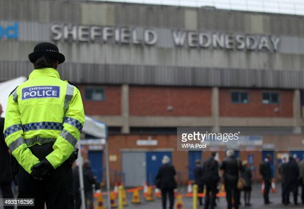 A police officer stands in front of members of the press outside the Hillsborough stadium in Sheffield as jurors on the inquest into the deaths of 96...