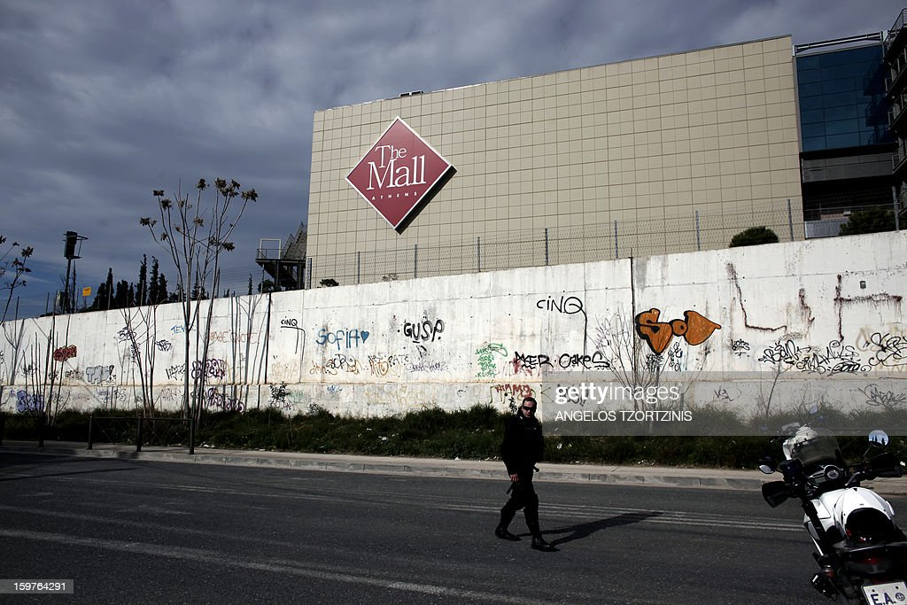 A police officer stands in front of multi-storey Athens Mall, in Athens on January 20, 2013. An explosive device went off in a garbage bin on the first floor of the multi-storey Athens Mall, in a northern suburb of the Greek capital, where shops as well as a branch of the National Bank of Greece are located, the police source said. AFP PHOTO / Angelos Tzortzinis
