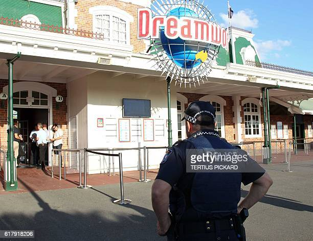 A police officer stands in front of the Dreamworld theme park on Gold Coast on October 25 after four people were killed when a park ride...