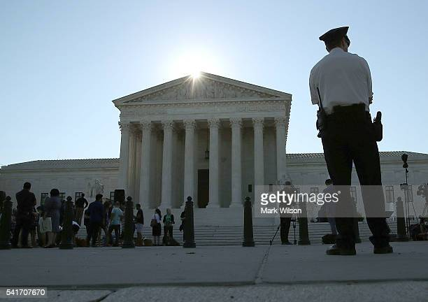 A police officer stands in front of the US Supreme Court building June 20 2016 in Washington DC The high court still has four decisions to hand down...