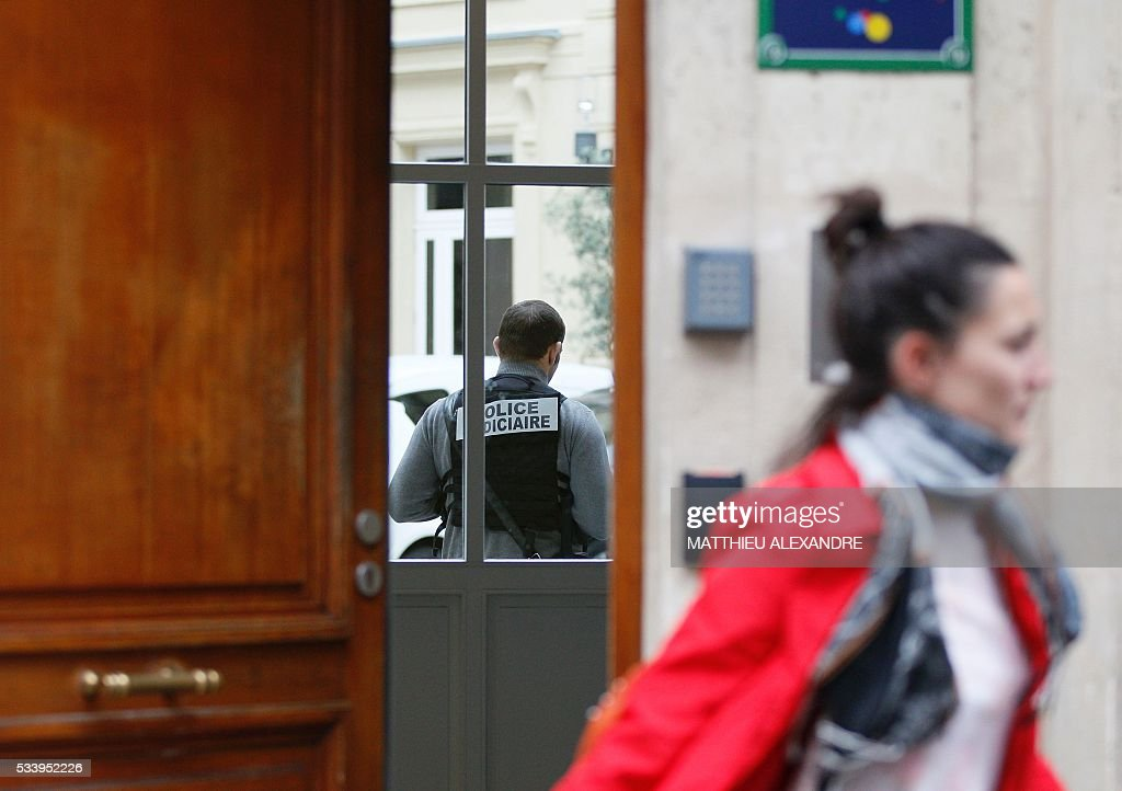A police officer stands in the Paris offices of US Internet giant Google on May 24, 2016, in Paris, as police carry out a search as part of a tax fraud investigation. French authorities believe Google owes 1,6 billion euros (USD 1,7 billion) in back taxes, a source close to the matter said in February. Google is one of several multinational corporations that have come under fire in Europe for paying extremely low taxes by shifting revenue across borders in an often complex web of financial arrangements.