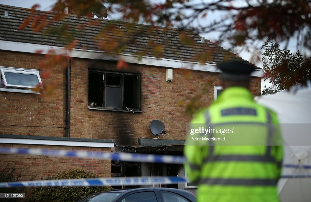 A police officer stands near a house where five people died in a fire on October 15, 2012 in Harlow, England. A woman and four children have died and another three are in hospital after a fire in a house on an estate near Harlow in Essex.
