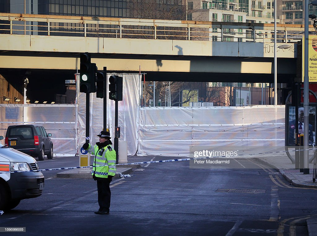 A police officer stands near barriers erected at the scene of a helicopter crash on January 17, 2013 in London, England. Police cordons have remained in place as investigations continue into the cause of yesterday's helicopter crash in which two people died.