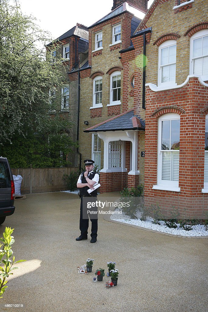 A police officer stands near floral tributes placed in the drive of a house in New Malden on April 23, 2014 in south London, England. Police say that a 43 year old woman has been arrested after the bodies of three children were found at a property last night.
