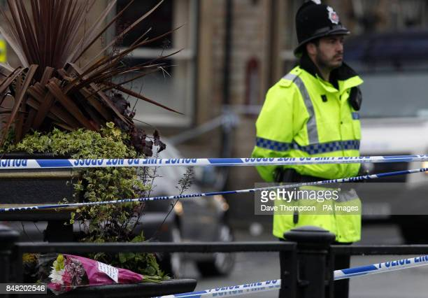 A police officer stands near flowers inside a cordon close to the scene of a suspected gas blast in Buckley Street in the Shaw area of Oldham Greater...