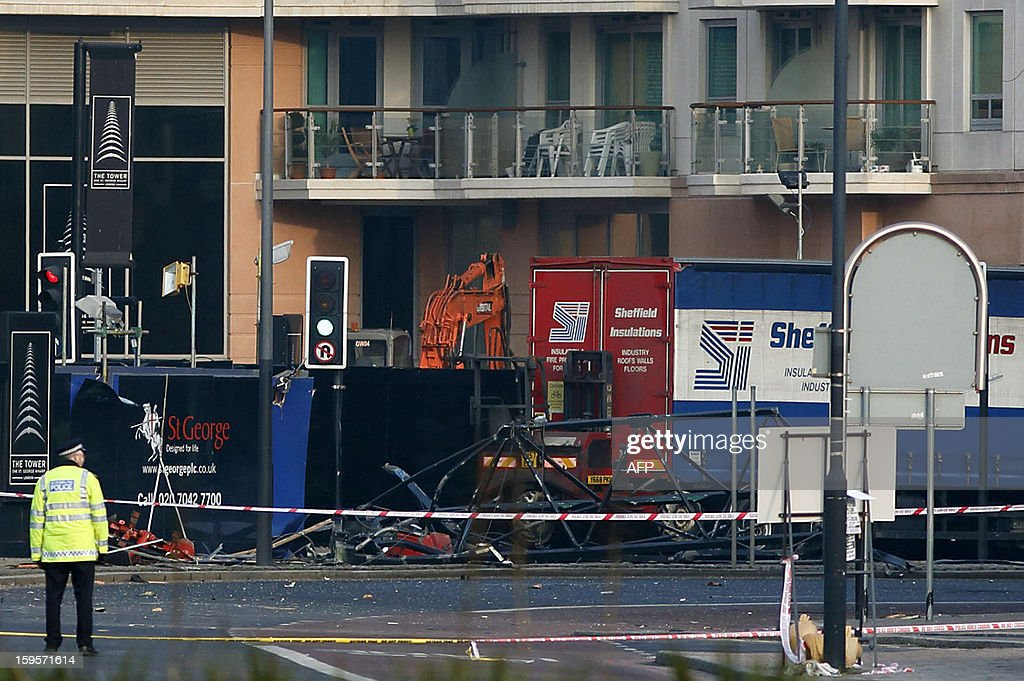 A police officer stands near part of the crane that was hit by a helicopter at the scene of the crash in central London on January 16, 2013. Two people were killed when a helicopter hit a crane at a building site in central London during morning rush hour and plunged to the ground, engulfing several cars in flames.