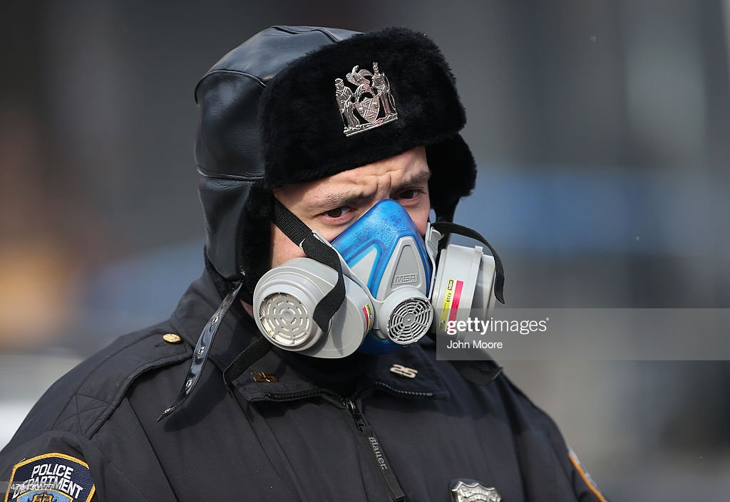 A police officer stands near the smoking site of an explosion in East Harlem on March 13, 2014 in New York City. At least 7 people were killed, according to reports, in Wednesday's explosion which collapsed two buildings on Park Avenue at 116th Street.