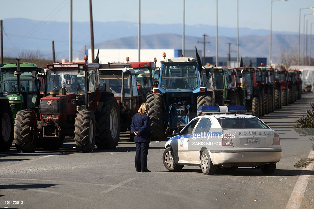 A police officer stands next to a police car on February 11, 2013 in front of parked tractors as farmers seek to block the highway between Thessaloniki and Athens in Nikaia, some 380 kms north of Athens. Protesting Greek farmers, who are demanding tax breaks and other benefits, have refused an offer from the Greek government after a February 10 meeting and they said they would not relent and keep their tractors positioned at key points on major roads across Greece, which they have continually threatened to blockade unless they get everything they want.