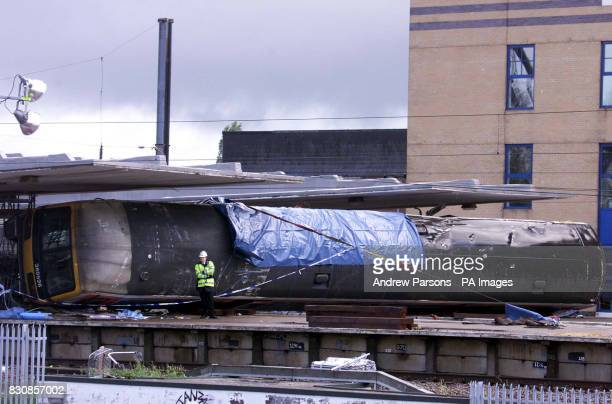 A police officer stands next to a railway carriage on Potters Bar station north of London where further attempts will be made later to remove it The...