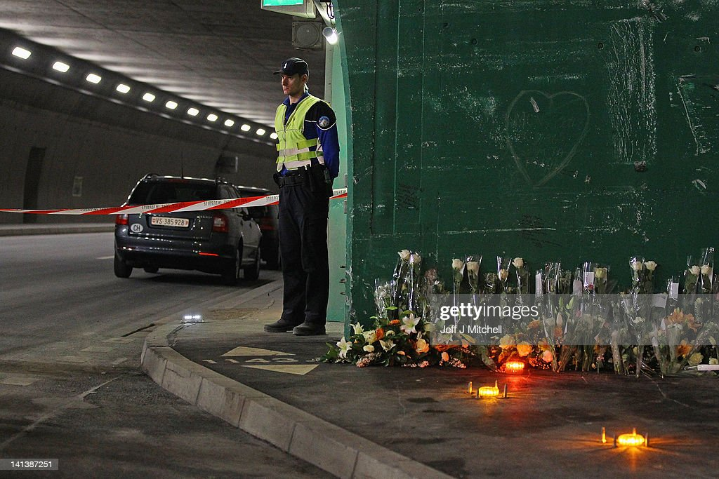 A police officer stands next to floral tributes laid by the families at the scene in the road tunnel where the 22 Belgian school children, four teachers and two drivers died in a coach crash, on March 15, 2012 in Sierre, Valais, Switzerland. The accident occurred on March 14, when a coach carrying 11-12 year old shcoolchildren returning from a skiing holiday crashed into a tunnel, killing 28 of the 52 passengers.