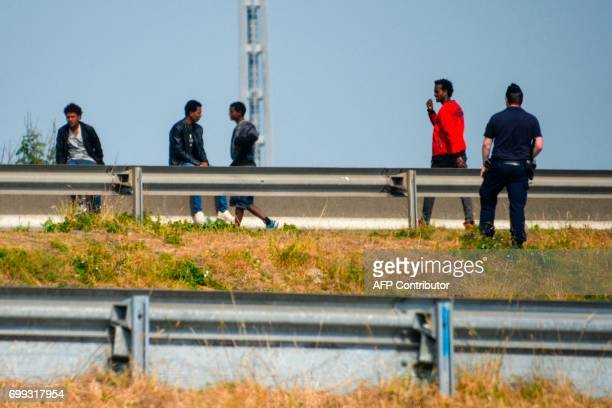 A police officer stands next to migrants waiting on the roadside along the ring road leading to the port of Calais northern France on June 21 2017 A...