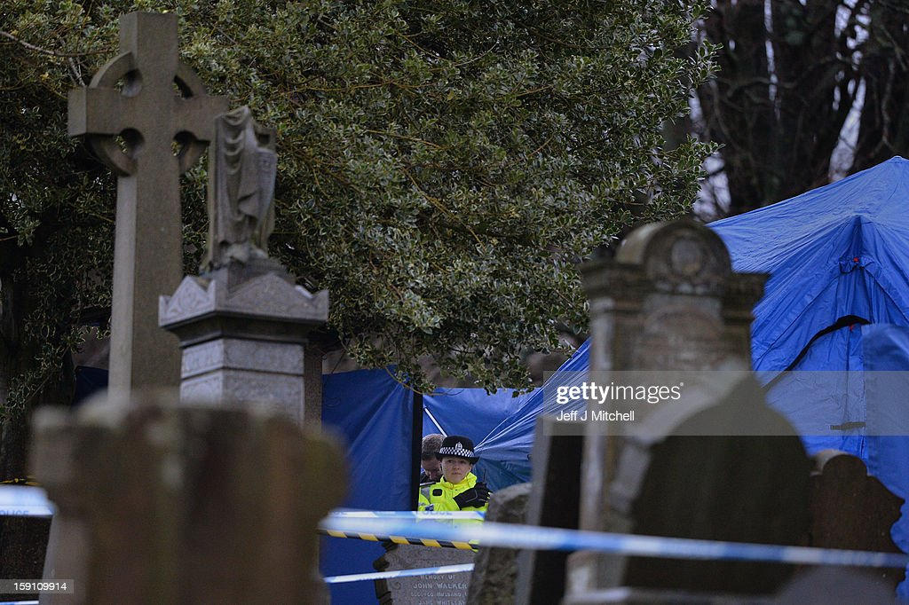 Police officer stands on duty at Monkland Cemetery as forensic officers start examining a burial plot on January 8, 2013 in Coatbridge, Scotland. Forensic specialist will exhume remains at a grave in North Lanarkshire in search for the body of 11 year old school girl Moria Anderson, who went missing, presumed murdered, in 1957.