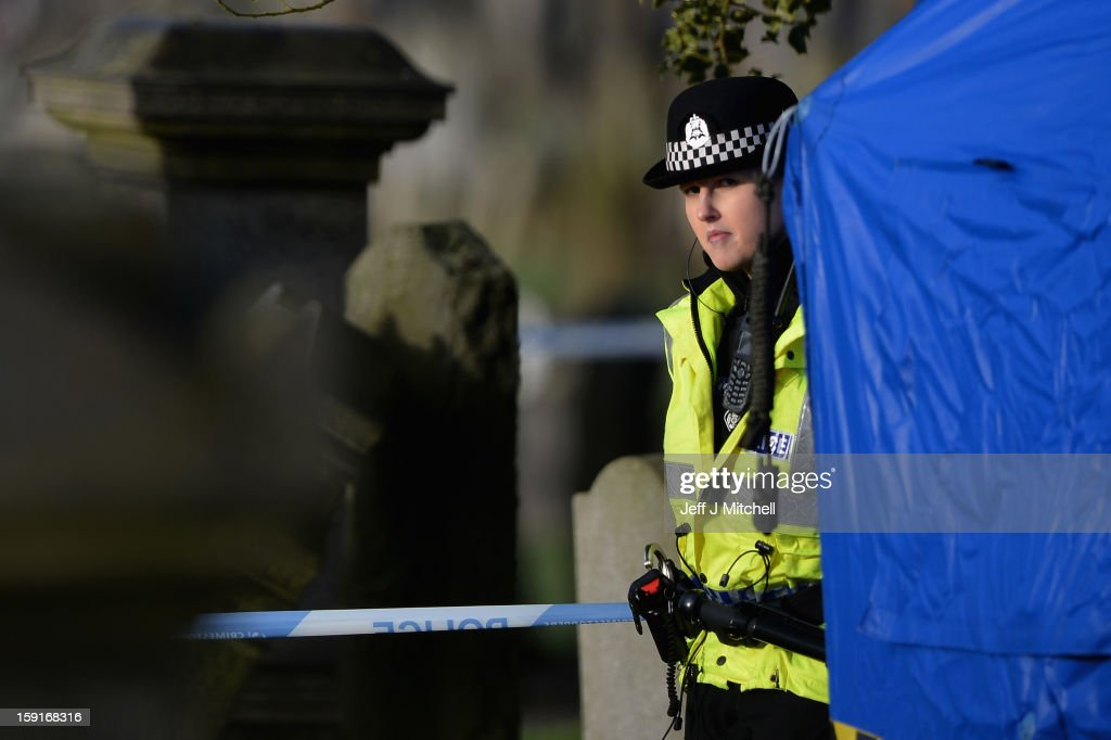 A police officer stands on duty at Monkland Cemetery as forensic officers continue to exame a burial plot on January 9, 2013 in Coatbridge, Scotland. Forensic specialists are exhuming remains at a grave, in search of 11 year old school girl Moria Anderson who went missing, presumed murdered in 1957.