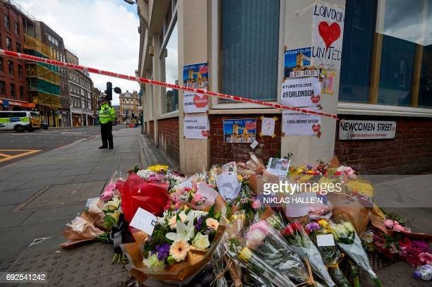 A Police officer stands on duty beyond flowers laid at a a cordon on Borough High Street near Borough Market in London on June 5 as they continue...