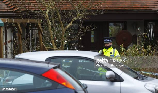A police officer stands outside a house in Smuggler's Lane Bosham West Sussex where a 55 year old woman was found murdered
