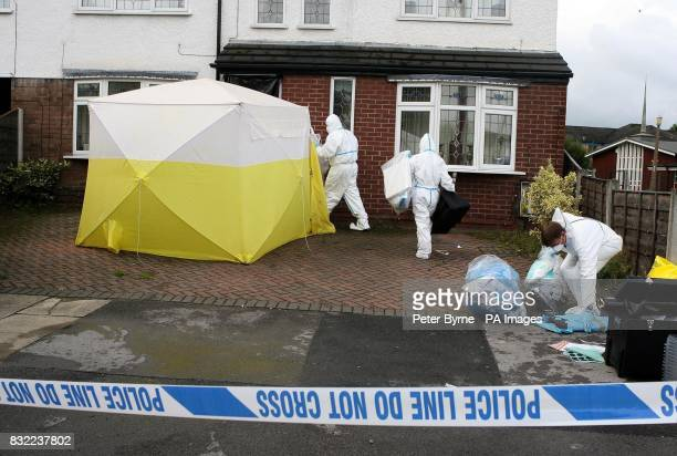 A police officer stands outside a house in Turves Road Cheadle Hulme in Manchester as a forensic team arrive