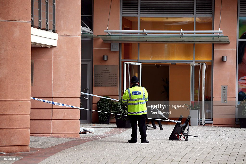 A police officer stands outside a residential bliock near to the scene where a helicopter crashed in Vauxhall, on January 16, 2013 in London, England. According to reports, the helicopter hit the crane attached to St Georges Wharf Tower before plunging into the road below during the morning rush hour. Two people died and nine casualties have been confirmed with one in a critical condition.