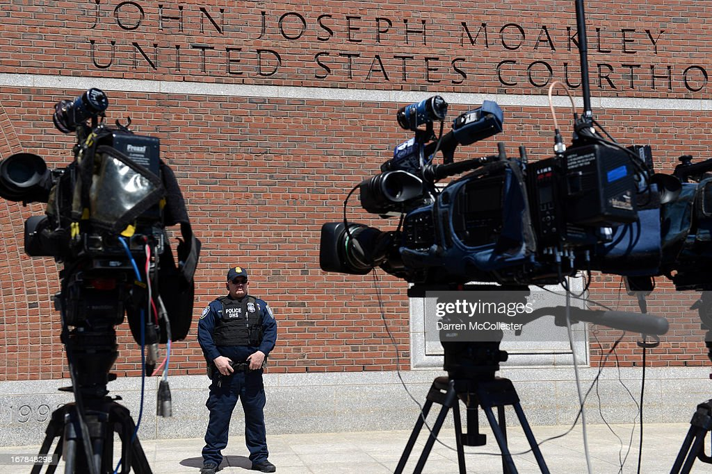 A police officer stands outside the John Joseph Moakley Courthouse in front of TV cameras after authorities arrested three men today in connection with the Boston Marathon bombings May 1, 2013 in Boston, Massachusetts. They are alleged to have helped the Tsarnaev brothers after the bombings. Two men, Azamat Tazhayakov and Dias Kadyrbayev, came to America to study at the University of Massachusetts at Dartmouth, where Dzhokhar Tsarnaev was also ernolled. The third person taken into custody is a U.S. citizen but was not identified.