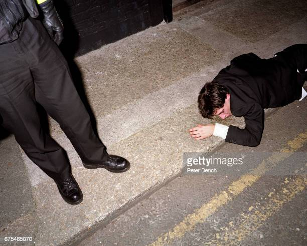 A police officer stands over a man found lying in the gutter near Union Street in Plymouth November 2001