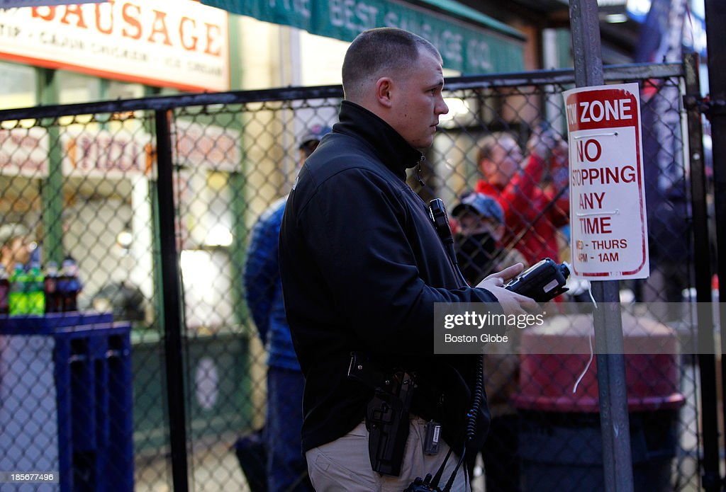 A police officer stands watch as fans enter the gate before the start of the game. The Boston Red Sox host the St. Louis Cardinals at Fenway Park for Game One of the 2013 Major League Baseball World Series, Oct. 23, 2013.