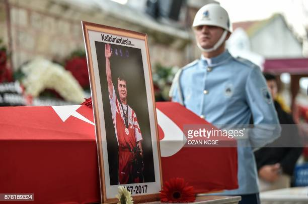 A police officer stays next to a coffin of Turkey's legendary triple Olympic goldmedal winning weightlifter Naim Suleymanoglu on November 19 2017...