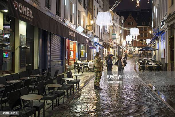 A police officer stops and searches a pedestrian as soldiers watch outside an empty restaurant terrace near Grand Place square in Brussels Belgium on...