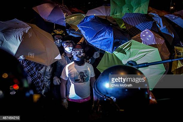 A police officer strikes at prodemocracy protesters during a clash with police on a street in Mong Kok on October 19 2014 in Hong Kong Hong Kong...