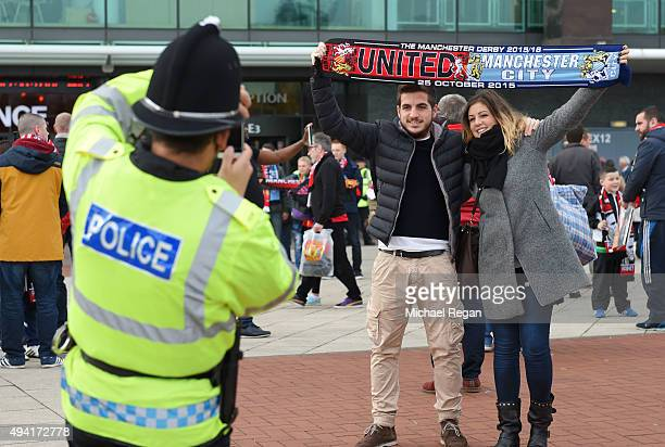 A police officer take photographs for fans prior to the Barclays Premier League match between Manchester United and Manchester City at Old Trafford...