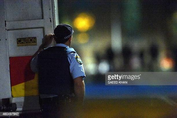 A police officer takes a behind a truck during an operation outo end a siege in a cafe in the central business district of Sydney on December 16 2014...