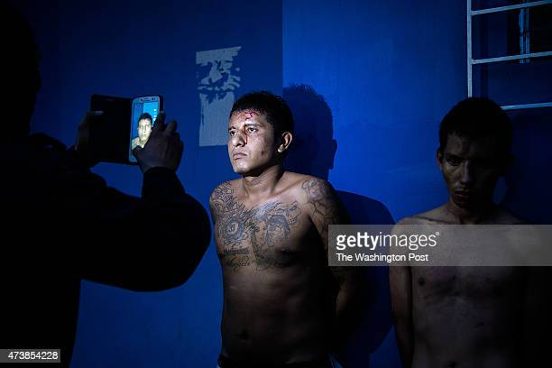 SALVADOR MAY 2015 A police officer takes a picture with his cell phone of a gang member of the El Barrio 18 Revolucionarios in San Salvador