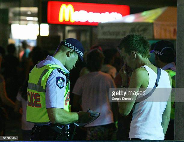 A police officer takes details from a young school leaver during the opening night celebrations of Schoolies week in Surfers Paradise on November 21...