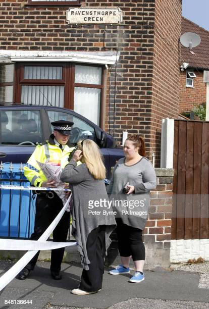 A police officer takes flowers from a family friend at the scene in the Norris Green area of Liverpool after a man was shot dead
