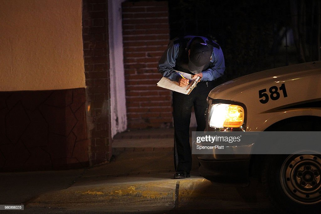 A police officer takes notes at an early morning murder, one of numerous murders over a 24 hour period, on March 26, 2010 in Juarez, Mexico. Secretary of State Hillary Rodham Clinton, Defense Secretary Robert Gates, and Homeland Security Secretary Janet Napolitano all visited Mexico on March 23 for discussions centered on Mexico's endemic drug-related violence. The border city of Juarez, Mexico has been racked by violent drug related crime recently and has quickly become one of the most dangerous cities in the world to live. As drug cartels have been fighting over ever lucrative drug corridors along the United States border, the murder rate in Juarez has risen to 173 slayings for every 100,000 residents. President Felipe Calderon's strategy of sending 7000 troops to Juarez has not mitigated the situation. With a population of 1.3 million, 2,600 people died in drug-related violence last year and 500 so far this year, including two Americans recently who worked for the U.S. Consulate and were killed as they returned from a children's party.