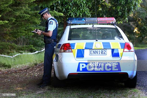 Police Officer takes notes outside the boundary of bush where a body was found at Matarangi Beach on January 3 2011 in Matarangi near Whitianga New...