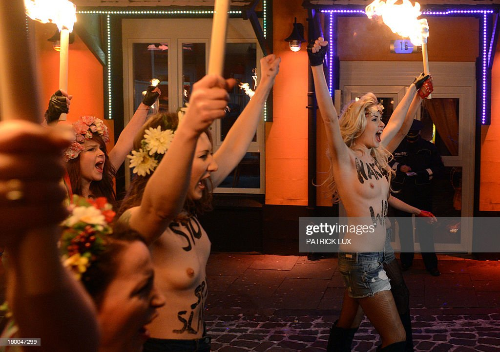 A police officer takes notes while bare chested activists of Femen, a Ukranian feminist movement, protest against prostitution as they walk with torches on Herbertstrasse , the the red light district in Hamburg, northern Germany on January 25, 2013. The activists . AFP PHOTO / PATRICK LUX