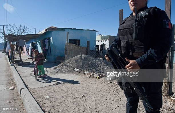 A police officer takes part in a security operation on February 13 2013 in a street of Ciudad Juarez Chihuahua state Mexico According to official...