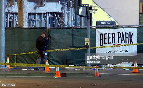A police officer takes photos as he investigates the scene on the Las Vegas Strip in front of the Paris Las Vegas where a car crashed into a group of...