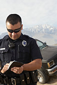 Police officer taking notes in front of car