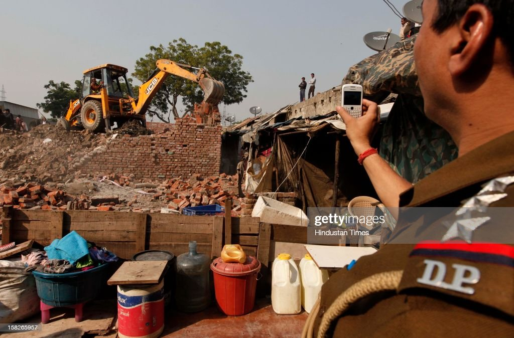 A Police officer taking photos on his mobile after a wall collapsed caused death of 5 children and serious injury to one child at Dallupura village near New Ashok Nagar on December 12, 2012 in New Delhi, India.