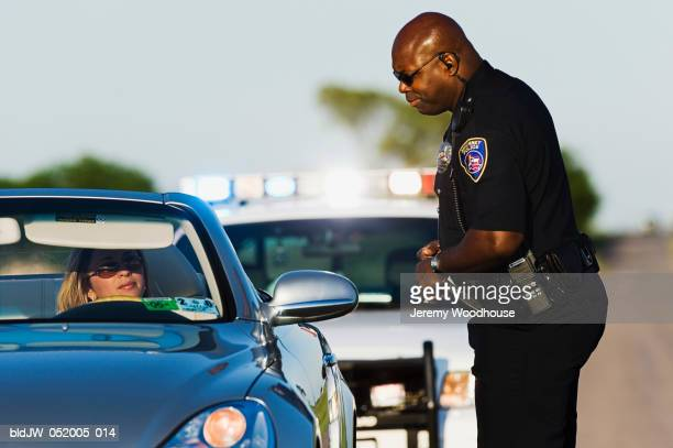 Police officer talking to a mid adult woman sitting in a car