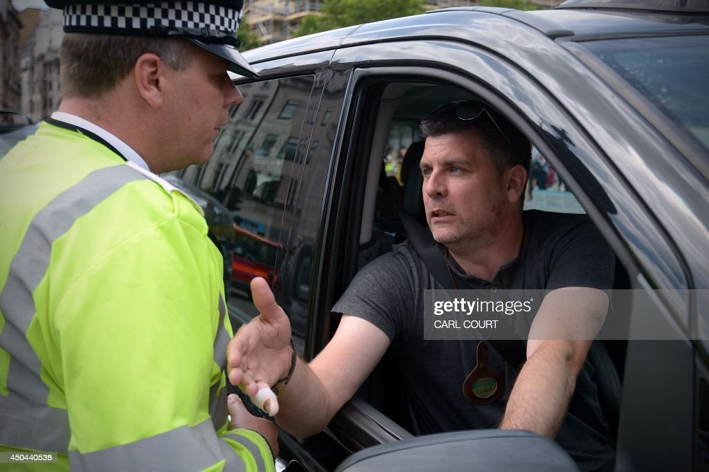 A police officer talks a London black cab driver during a protest against a new private taxi service 'Uber', a mobile phone app, in central London on June 11, 2014. Taxi drivers brought parts of London, Paris and other European cities to a standstill on June 11 as they protested against new private cab apps such as Uber which have shaken up the industry. Thousands of London's iconic black cabs, many of them beeping their horns, filled the roads around Buckingham Palace, Trafalgar Square and the Houses of Parliament to the exclusion of any other vehicles.