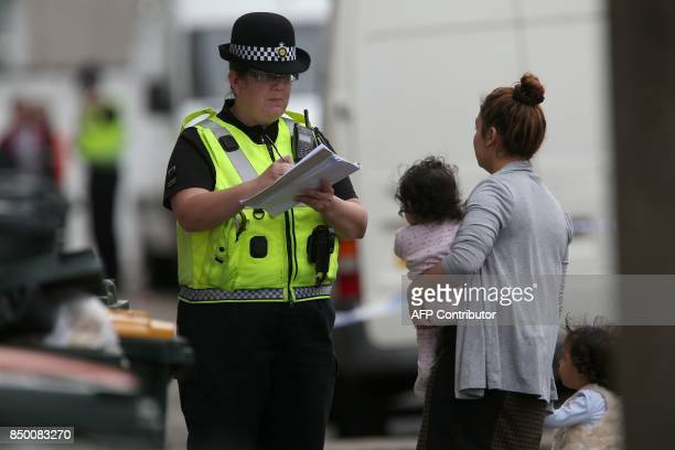 A police officer talks with local residents at a police cordon near to a house in Newport south Wales on September 20 as they continue their...