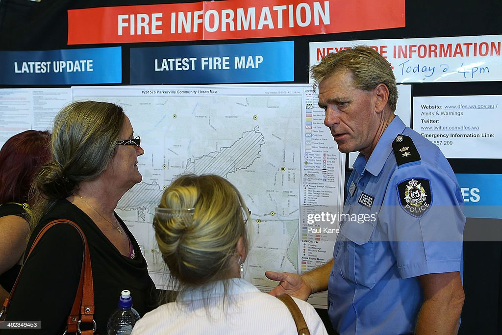 A police officer talks with residents during an afternoon community meeting to advise home owners of the current fire situation at the Brown Park community centre on January 13, 2014 in Perth, Australia. Evacuated residents of Perth Hills are awaiting permission to access and inspect their properties after a bushfire blazed through the suburb, destroying over 46 homes. Emergency services are assessing the affected area and expected the number of properties damaged to increase.