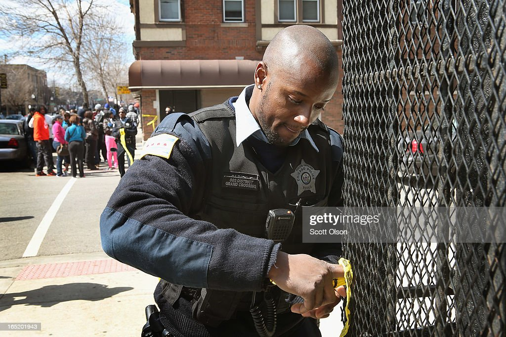A police officer tapes off the crime scene where a 24-year-old man was shot and killed on South Eberhart Avenue on the city's South Side April 1, 2013 in Chicago, Illinois. According to published reports, the man was the 73rd homicide victim and the 39th victim under the age of 25 in Chicago in 2013.