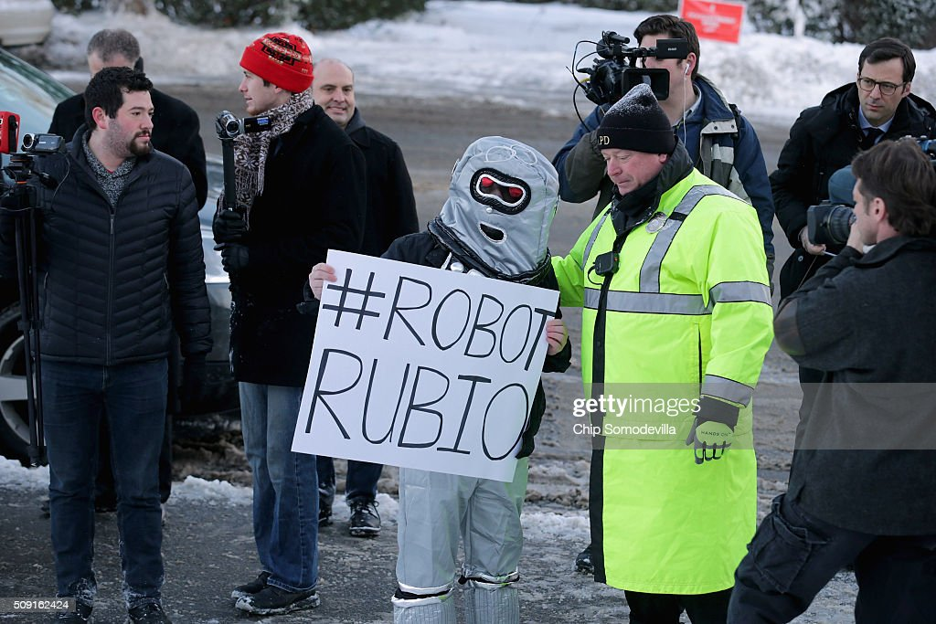 A police officer tells a demonstrator from the American Bridge 21st Century super PAC that he can not block the sidewalk outside the polling place outside Webster School February 9, 2016 in Manchester, New Hampshire. With a good showing in the Iowa caucuses, Republican presidential candidate Sen. Marco Rubio has stepped into the crosshairs of fellow Republicans running for president and super PACs that want to slow his momentum with attacks on what they call his robotic and repetative messaging.