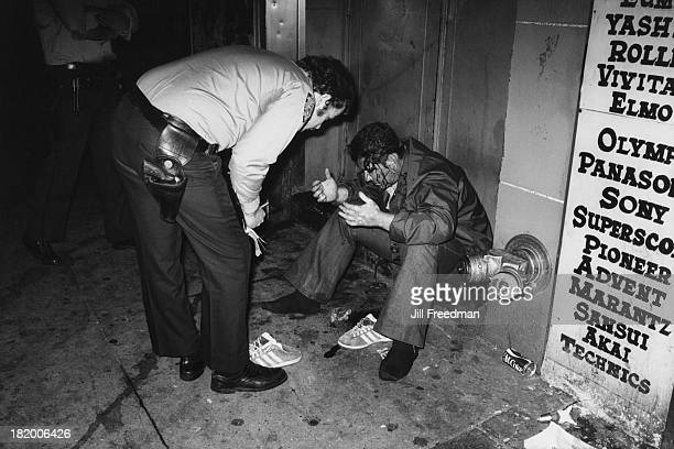 A police officer tends to an injured man at 4 am near Times Square New York City circa 1979