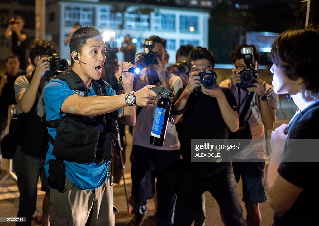 A police officer threatens to pepper spray a prodemocracy protester as demonstrators tried to occupy a main road in Hong Kong on October 15 2014 Hong...