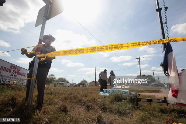 A police officer ties off crime scene tape near the First Baptist Church of Sutherland Springs on November 7 2017 in Sutherland Springs Texas On...
