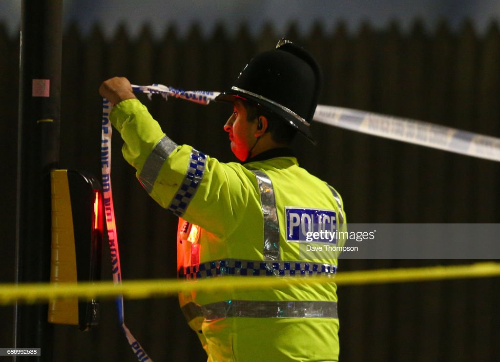 MANCHESTER, ENGLAND - A police officer ties police crime scene tape close to the Manchester Arena on May 23, 2017 in Manchester, England. There have been reports of explosions at Manchester Arena where Ariana Grande had performed this evening. Greater Manchester Police have have confirmed there are fatalities and warned people to stay away from the area.