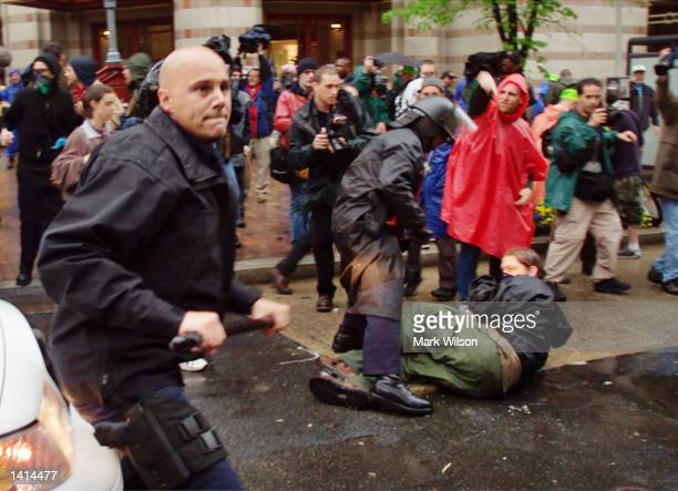 A police officer tries to fend off protesters who were blocking a road April 17 2000 in Washington DC Hundreds of people are taking part in...